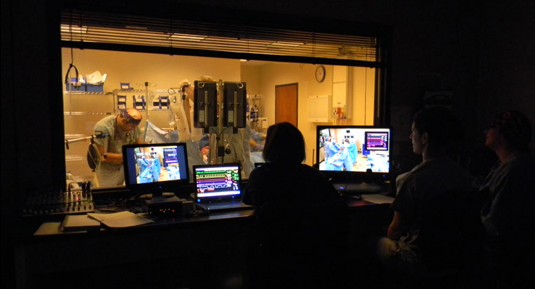 Simulation specialist controls vital signs of patient mannequin while faculty members observe resident